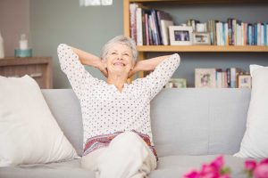 Senior woman relaxing on sofa after retirement home construction