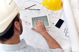 commercial general contractor studies blueprints from architect