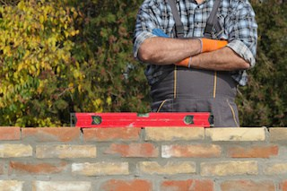 general contractor inspects quality of work and if brick wall is level
