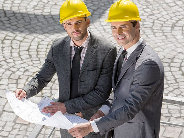 hotel renovation costs considered by two executives with yellow hard hats on