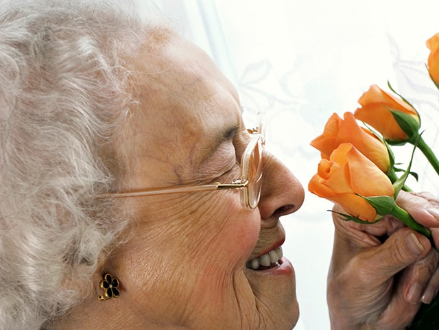 building an assisted living facility for elderly woman smelling flowers