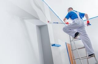 Pintura comercial y renovación con contratista en escalera.