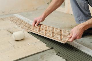 contratista de azulejos colocando un borde decorativo para la construcción comercial