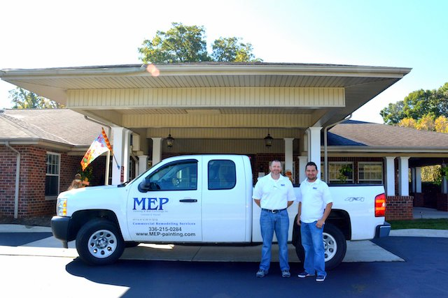 professional mep contractors stand in front of truck after commercial remodeling project